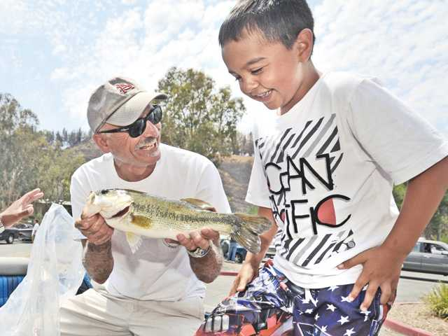 "Squeemish Isaac Chippes, 8, right, backs away as Angler All Hasson displays one of the big mouth bass caught by Isaac's dad, Sergio, a U.S. Army veteran during the Top Stick Tour - ""Day on the Lake"" fishing tournament at Castaic Lake on Saturday."