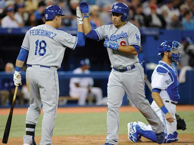 Los Angeles Dodgers' Jerry Hairston Jr., center, high fives teammate Tim Federowicz (18) after scoring a solo home run during the sixth inning  against the Toronto Blue Jays on Tuesday in Toronto.