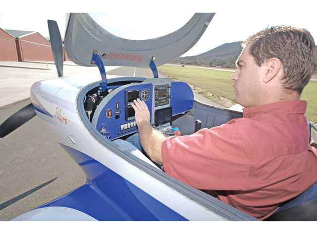 Brandon Cangiano describes the cutting-edge electronics in his home-built Lancair Legacy airplane at Agua Dulce Airport. Signal photo by Dan Watson