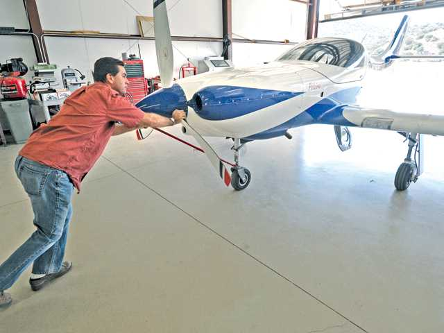 Brandon Cangiano pushes his home-built Lancair Legacy airplane out of the hangar at Agua Dulce Airport. Signal photo by Dan Watson