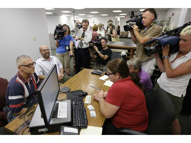 Marcus Saitschenko, left, and James Goldstein obtain a marriage license despite a state law banning such unions on Wednesday in Norristown, Pa.