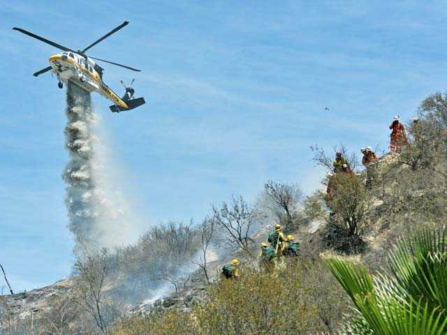 A Los Angeles County Fire helicopter drops water as crews mop up following a brush fire near Sierra Estates Drive and Ridge Vale Drive in Canyon Country on Thursday. Signal photo by Jonathan Pobre