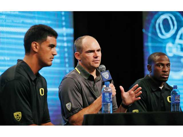 Oregon coach Mark Helfrich, center, talks to reporters as he is flanked by quarterback Marcus Mariota, left, and cornerback Ifo Ekpre-Olomu during Pac-12 Conference Media Day Friday in Culver City.
