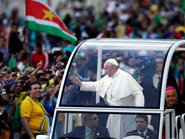 Pope Francis waves from his popemobile in Rio de Janeiro, Brazil on Friday. He also heard confessions from young pilgrims in a park and met with juvenile detainees.