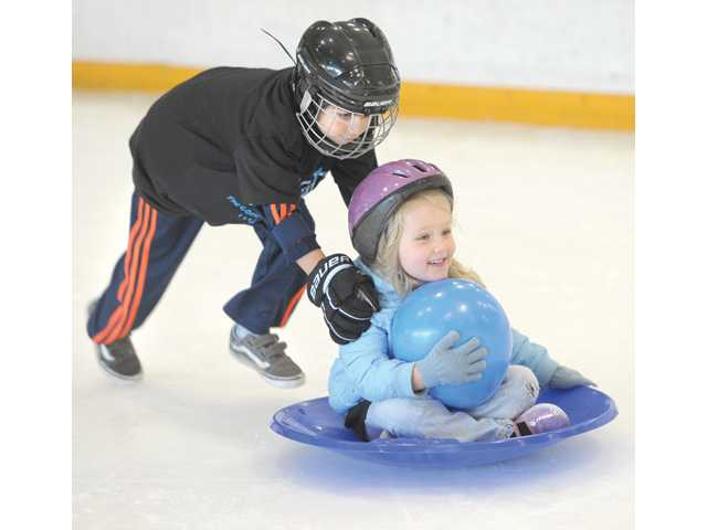 Zach Cooper, 6, pushes Emme Robertson, 4, as they race other participants of the Kidtastic Summer Skating Camp at Ice Station Valencia, avoiding the muggy 84 degree heat outside on Friday.