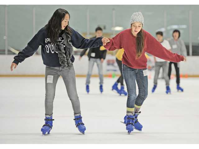 Joan Shim, left, assists novice skater Victoria Mejia, 13, wearing sweatshirts and a knitted cap, as they avoid the muggy, 84 degree, outside while ice skating during the afternoon public skate at Ice Station Valencia on Friday.