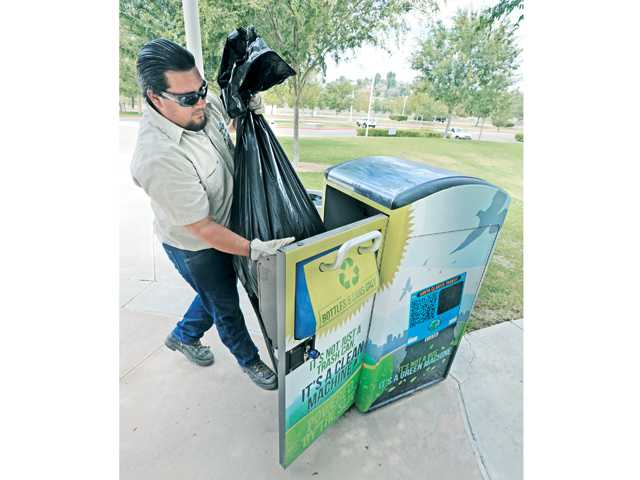 Seasonal park maintenance worker Alex Basaldu pulls a bag of compacted recycled bottles and cans from one of eight solar-powered BigBelly compactors located at Central Park in Saugus on Friday.