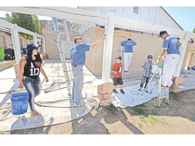 Brittany Magno, 18,  left,  brings water in a bucket for A. Allbright Painting Inc. volunteers as they paint the exterior of her home in Canyon Country on Saturday as part of the 8th Annual Paint It Forward, charity paint makeover.