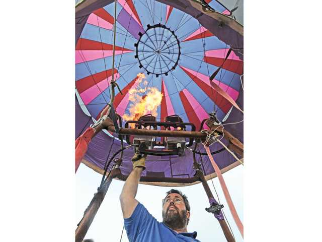 Balloon pilot Tom Pratt of Ontario lights the burner to raise his balloon,  Restless, at the sixth Annual Citrus Classic  Balloon Festival held in Santa Paula on Saturday.  Signal photo by Dan Watson.