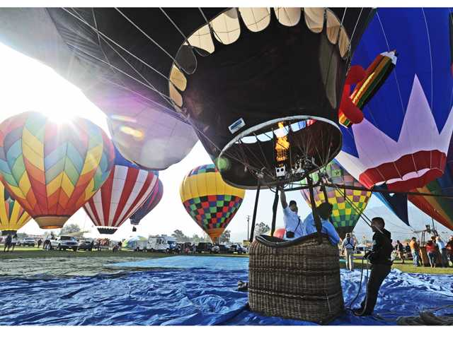 "The crew of Panda ""Air"" Balloon Flights hit the burners to keep the envelope filled with hot air as they join some-30 crews to display their balloon at the sixth Annual Citrus Classic  Balloon Festival held in Santa Paula on Saturday. Signal photo by Dan Watson."