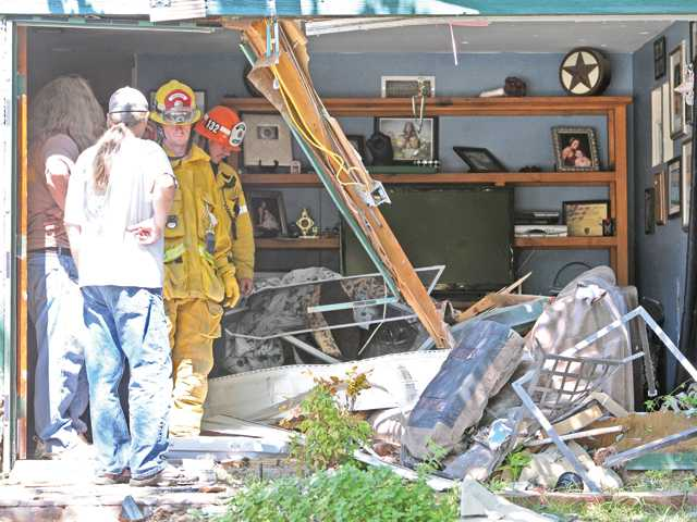 Firefighters examine the damage to the front room of a home on Wistaria Valley Road in Canyon Country where a late model Honda Accord four door sedan crashed into the home, injuring multiple people on Saturday afternoon.