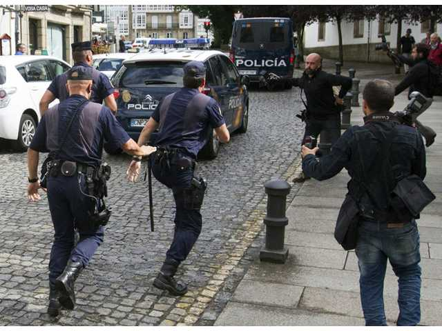 Media run after a police car carrying arrested train driver Francisco Jose Garzon Amo, unseen, to testify in court in Santiago de Compostela, Spain on Sunday.