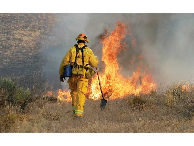A Los Angeles County firefighter approaches a fire along a blaze which was part of the Powerhouse Fire in Lake Hughes on June 2. Overall, the fire burned more than 30,000 acres.