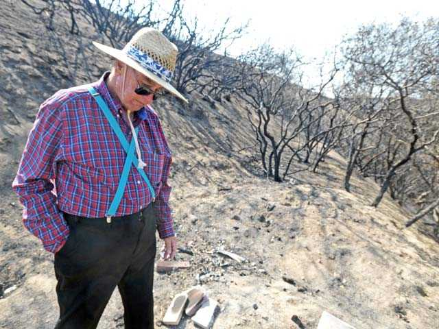 Chester Wilcox, a former resident of Lake Hughes, pauses as he walks through the property on which he used to live on Lake Hughes Road on Thursday. Photo by Jonathan Pobre/The Signal