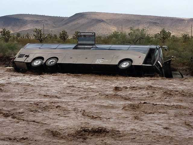A Las Vegas-bound tour bus lies on its side in a flooded desert wash near Dolan Springs, Ariz. on Sunday after being swept away by floodwaters amid heavy rains.