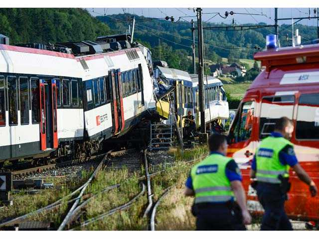Rescue personnel work at the site where two passenger trains collided head-on in Granges-pres-Marnand, western Switzerland, on Monday.