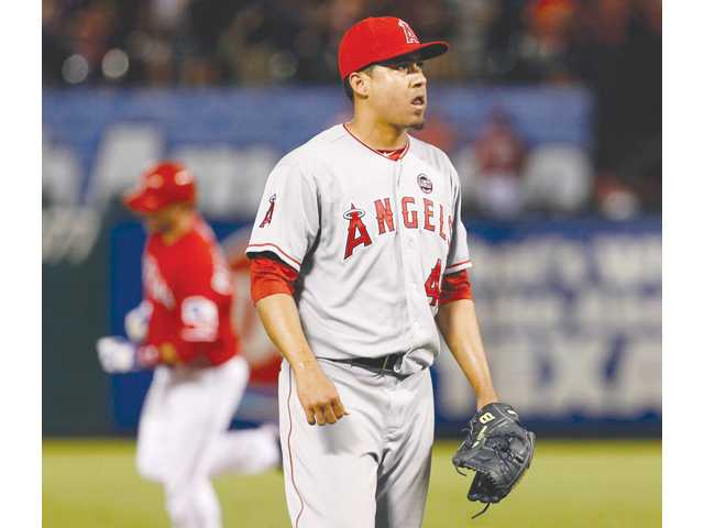 Los Angeles Angels relief pitcher Ernesto Frieri waits for a new ball after giving up a home run to Texas Ranger A.J. Pierzynski, background on Monday in Arlington, Texas.