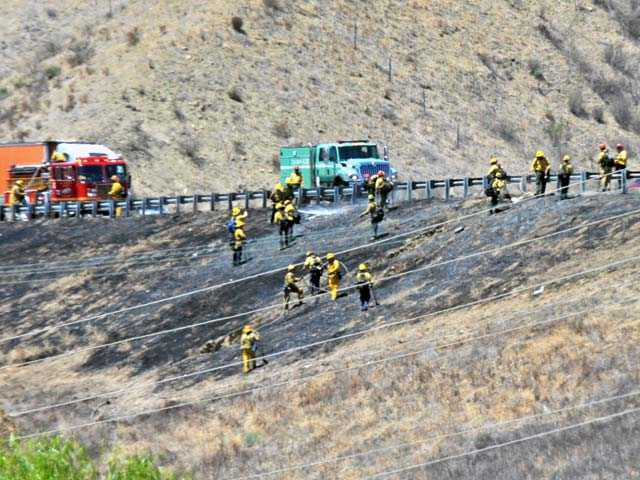 Firefighters mop up after a fire charred less than one-half of an acre of brush off the southbound lanes of Interstate 5 north of Lake Hughes Road in Castaic on Tuesday.