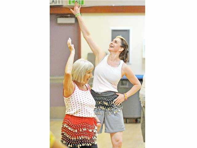 Doris Sipotz, left, and Jordana Capra enjoy a Zumba Gold fitness class at the Santa Clarita Valley Senior Center in Newhall on Monday. Photo by Jonathan Pobre.