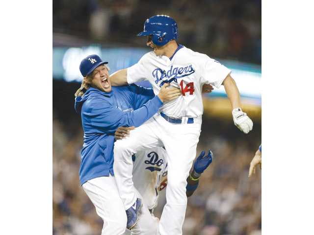 Los Angeles Dodgers second baseman Mark Ellis, right, celebrates with teammate Clayton Kershaw after driving in the winning run against the New York Yankees during the ninth inning in Los Angeles on Tuesday.