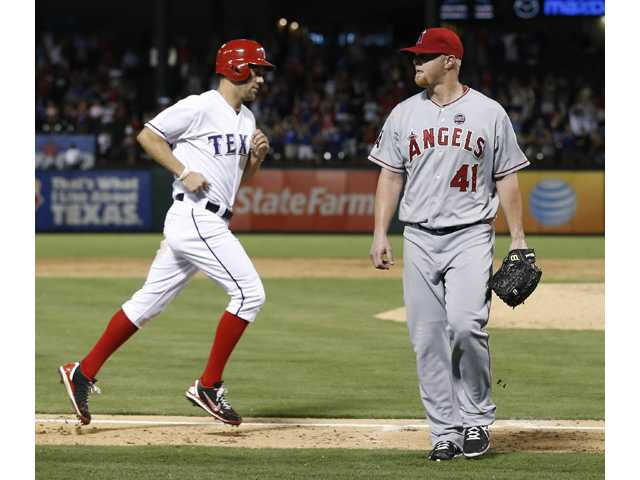 Los Angeles Angels pitcher Daniel Stange (41) leaves t=he field in front of Texas Ranger David Murphy, left, after the Rangers hit a walk-off home run Tuesday in Arlington, Texas.