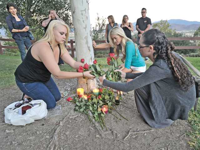 From left, Lisa Keating, Lindsay Reimars, and Stefanie Tidwell lay flowers in remembrance of their friend Rosemary Flynn at a vigil attended by family and friends at Canyon Country Park on Wednesday. Photo by Dan Watson.