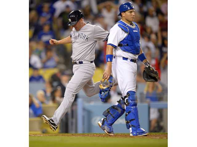 New York Yankee Lyle Overbay, left, scores on as Los Angeles Dodgers catcher A.J. Ellis looks on Wednesday in Los Angeles.