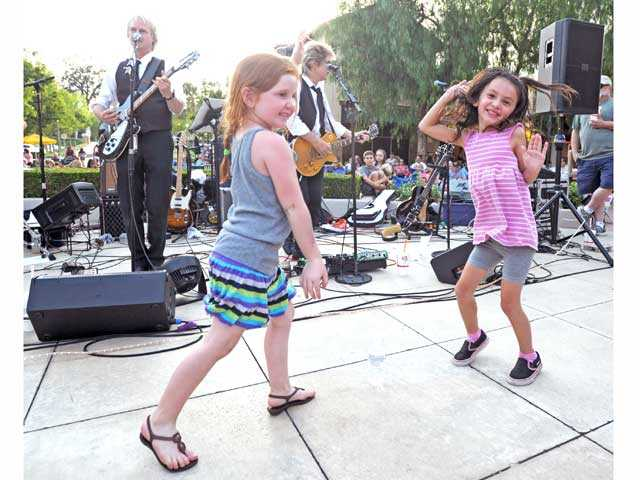 Kaydence Done, foreground left, and Emilee Reed, right, both 5, dance to the music of Sgt. Pepper as guitarists Bill Horn, background left, and Tom Kolb perform at Valencia Marketplace on Friday.