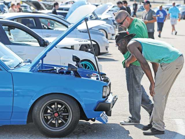 Juan Ochoa, top,  and Freddy Johnson look under the hood of a 1982 Corolla DX on display at the Santa Clarita Hot Import Car show held in the College of the Canyons Parking lot in Valencia on Saturday.