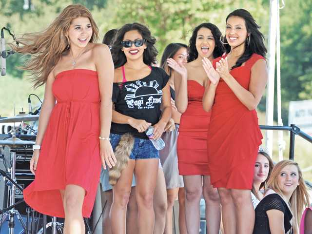Alecia Gonzalez, left, is cheered on by the other contestants  of the Valencia KIA Car Show Hottie contest.