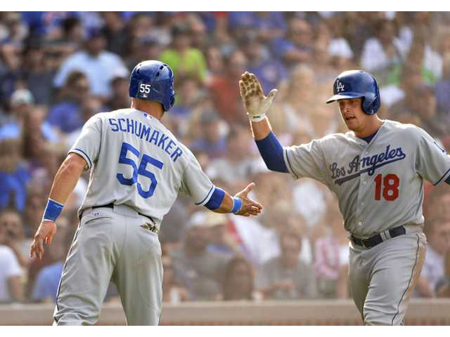 Los Angeles Dodgers' Tim Federowicz high-fives Skip Schumaker (55) after they scored on an RBI single hit by teammate Carl Crawford during the sixth inning against the Chicago Cubs on Saturday in Chicago.