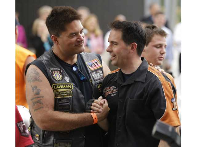 Wisconsin Governor Scott Walker, right, shakes hands with a Harley Davidson rider at the museum Friday in Milwaukee.