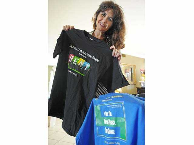"Leslie Berra holds souvenir t-shirts from theater productions ""Rent"" and ""You're Perfect, Now Change."""