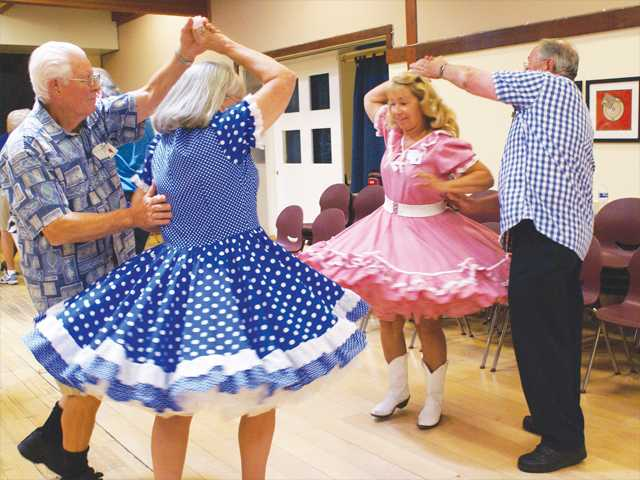 Palmdale's Aces & Deuces square dancers Mike Woods (left) with his wife and dance partner Janet Woods do some synchronized spinning with fellow members Roberta Searcy and Denny Sellers at a summer celebration sponsored by the Sierra Hillbillies Square Dance Club Sunday at the Santa Clarita Valley Senior Center in Newhall. Photo By Jim Holt.