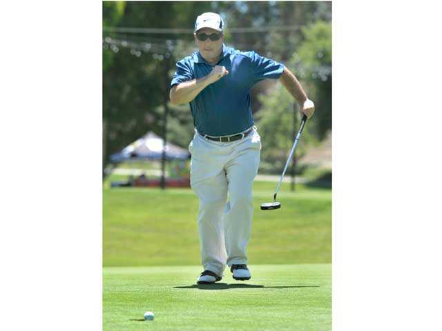 Mike Peluso reacts as he sinks his putt on the 18th hole at Valencia Country Club during the College of the Canyons Foundation Golf Tournament on Monday. Signal photo by Jonathan Pobre