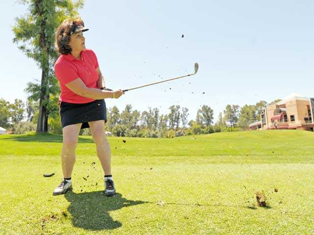 Tamara Gurney watches her shot toward the 18th hole at Valencia Country Club during the COC Foundation Golf Tournament on Monday. Signal photo by Jonathan Pobre