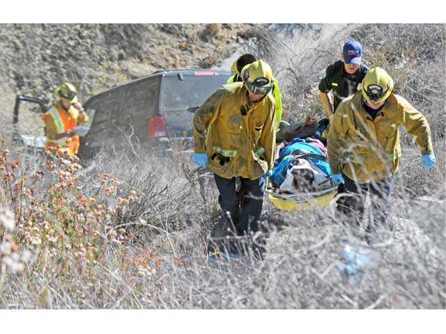 Firefighters and emergency medical technicians take a patient to a waiting ambulance after her SUV crashed in a ravine in Canyon Country. Signal photo by Jonathan Pobre