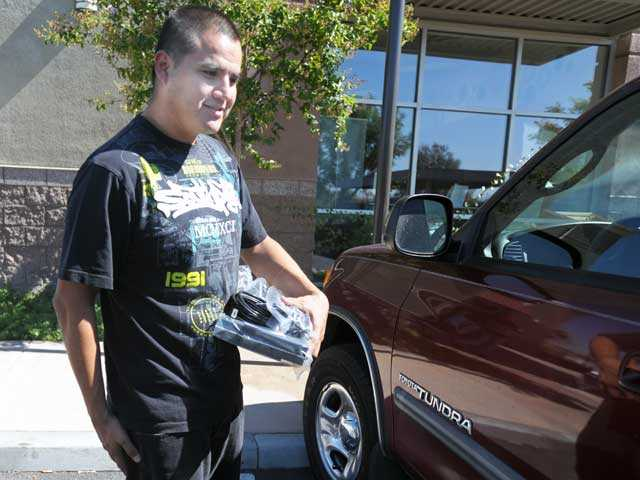 Lee Ochoa of Canyon Country carries a cable box to his car after upgrading his service with Time Warner on Monday. Signal photo by Jonathan Pobre