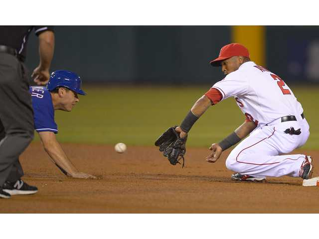 Texas Ranger Ian Kinsler, left, is caught off the bag and tagged out by Los Angeles Angels shortstop Erick Aybar on Monday in Anaheim.