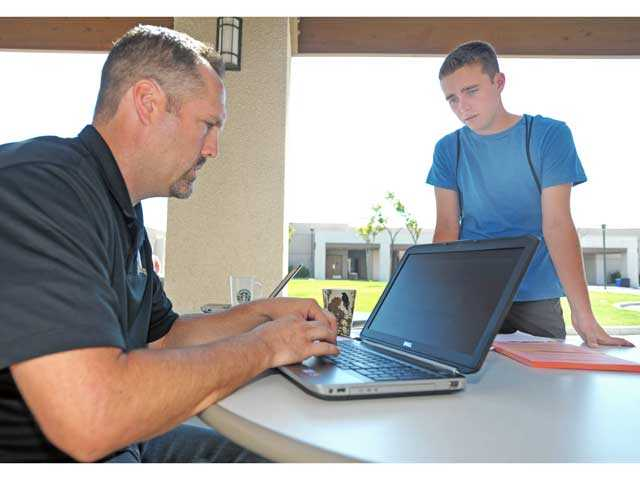 Counselor Travis Wiese, left, processes a class change for incoming senior Cody Rightmyer as students register for classes at Golden Valley High School in Santa Clarita on Tuesday. Photo by Jonathan Pobre.