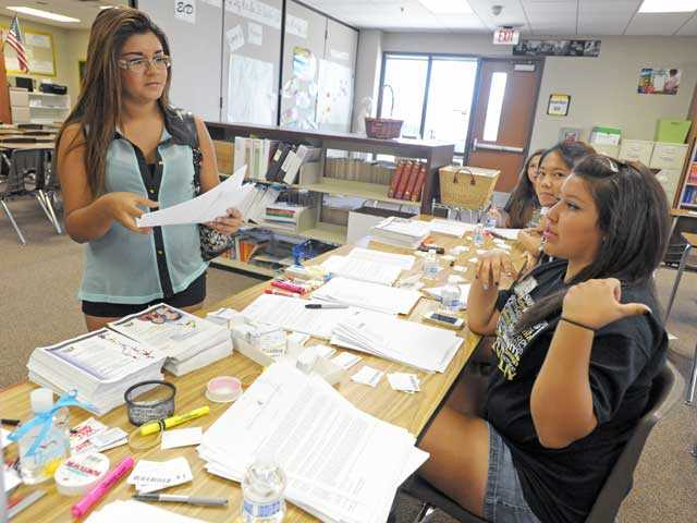 Lizeth Mendez, left, picks up her temporary ID card and class schedule as Ysaura Landeros, right, guides her to the next step in registering for classes at Golden Valley High School in Santa Clarita on Tuesday. Photo by Jonathan Pobre.