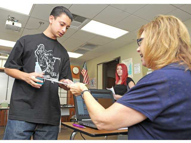 Incoming senior Pedro Morales, left, hands his emergency information card to health services technician Jill Stirling as he registers for classes at Golden Valley High School in Santa Clarita on Tuesday. Photo by Jonathan Pobre