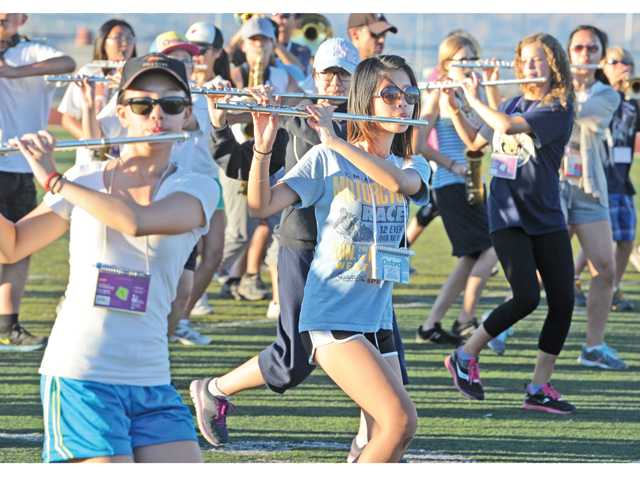 "Janice Youn, center, and members of the woodwind section of the West Ranch High School Marching rehearse music from the ""The Heist,"" as well as their choreography on the school's football field in Stevenson Ranch on Wednesday. Photo by dan Watson."