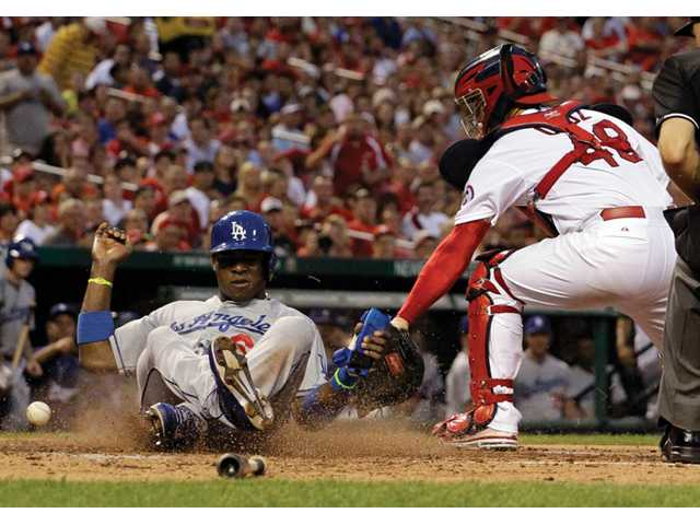 Los Angeles Dodger Yasiel Puig, left, scores past St. Louis Cardinals catcher Tony Cruz on Wednesday in St. Louis.