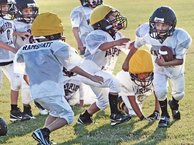 Drew Jara, 6, right,  takes a kickoff during practice with his team of Warrior Gremlins, ages 6 and 7, at Heritage Park in Valencia on Tuesday.