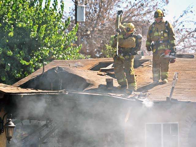 Firefighters break through the roof of a Newhall home after fire erupted in the garage of the residence and spread into the house. Two dogs and two cats were killed in the blaze, and one person was taken to the hospital with minor burns. Signal photos by Jonathan Pobre