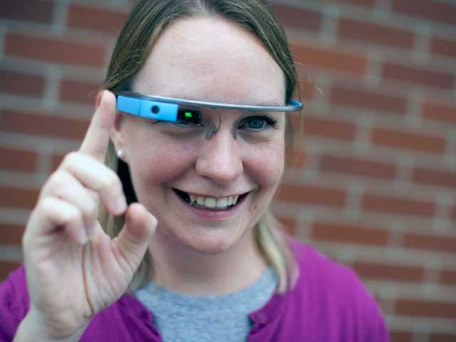 In this July 2013 photo, Marianne Kruppa, department manager for Sights and Sounds at St. Joseph County Public Library, wears a Google Glass device outside of the library in downtown South Bend, Ind.