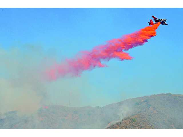 "An aircraft drops fire retardant over a hillside off San Francisquito Canyon Road as the ""Bee Fire"" burns over Santa Clarita on Friday."