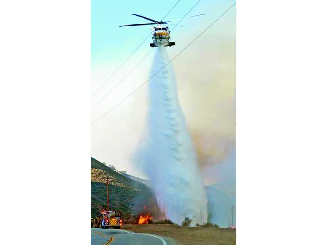 "A helicopter drops water over a hillside off San Francisquito Canyon Road as the ""Bee Fire"" burns over Santa Clarita on Friday."
