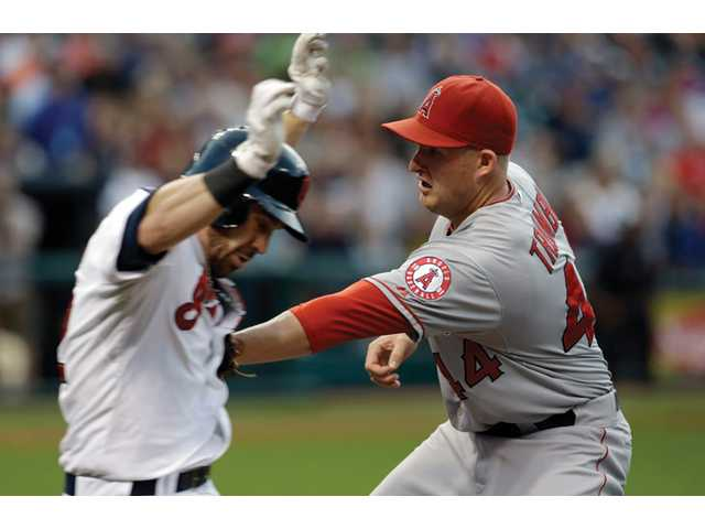 Los Angeles Angels first baseman Mark Trumbo, right, tags out Cleveland Indians' Jason Kipnis as he runs to first base Friday in Cleveland.